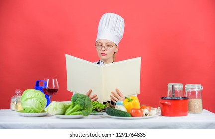 Culinary school concept. Female in hat and apron knows everything about culinary arts. Culinary expert. Woman chef cooking healthy food. Girl read book top best culinary recipes. Traditional cuisine.