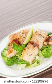 Culinary seafood eating. Grilled fish fillet with fresh rocket and lettuce salad on plate isolated on brown background.