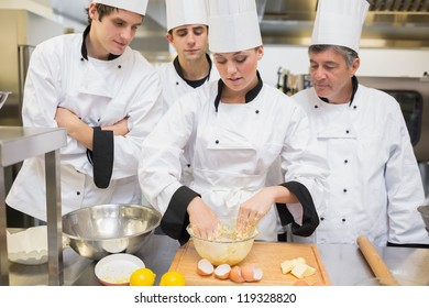 Culinary students learning how to mix dough in kitchen