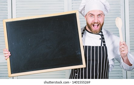 Culinary training. Chief cook teaching master class in cooking school. Man holding wooden spoon and blackboard. Master cook giving cooking class. Education of cooking and food preparation, copy space.