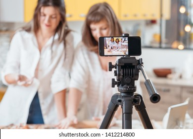 Culinary vlog. Two women baking shooting smartphone video tutorial. Content creating equipment. Online business hobby.