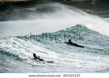 CULLEN, SCOTLAND - OCTOBER 21, 2013: Surfers heading out to sea while surfing near Cullen in Scotland during winter.