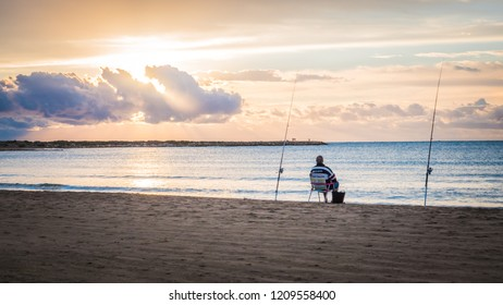 Cullera, Spain - 10 09 2018: An inspirational photo of an angler sitting on a chair on a beach by the Mediterranean Sea at sunrise. It was taken on the Racó beach in Cullera, Valencia, Spain, Europe.