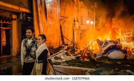 Cullera, Valencia / Spain - 02 19 2017: Falleros in Valencian tradicional clothes take photo at burning Falla during la Crema final event during Las Fallas festival in Valencia Community in Spain.