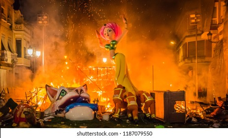 Cullera, Valencia / Spain - 02 19 2017: Fire men moving the rests of burning Falla Taut into the fire during la Crema final event during Las Fallas festival in Valencia Community in Spain.