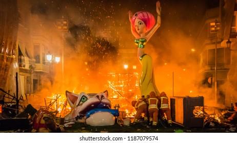 Cullera, Valencia / Spain - 02 19 2017: Fire men push the rest of burning Falla Taut into the fire during la Crema final event during Las Fallas festival in Valencia Community in Spain.