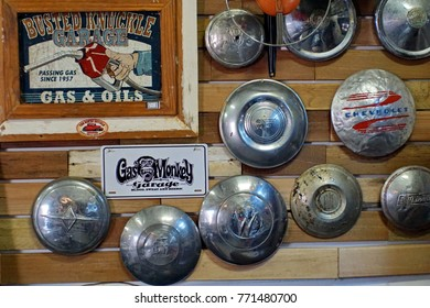 CULLINAN, SOUTH AFRICA - CIRCA SEPTEMBER 2017: Retro mechanic's signs and old hubcaps at a small motorcycle gift shop across from the train station