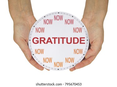 Cultivate a GRATITUDE attitude NOW  - female hands holding a clock with no hands that has NOW in place of the numerals and GRATITUDE instead of hands isolated on a white background