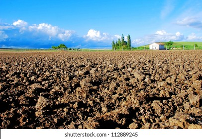 Cultivated field with a house in the distance and blue sky