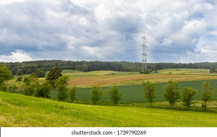 Cultivated fields in Germany. Cereal cultivation. Single high voltage pole. Ripening cereals. Red poppies in the field. Cloudy sky
