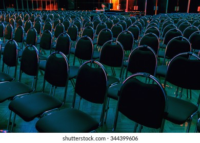 Cultural hall with chairs in rows, colorfully lit, selective focus.