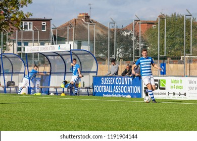 Culver Road, Lancing, UK; 30th September 2018; Player Dribbles With ball While Two Substitutes Warm Up at side of Pitch During Amateur Football Match Between Hillside Rangers FC v Horsham Crusaders FC