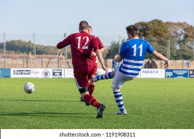 Culver Road, Lancing, UK; 30th September 2018; Player Strikes Ball While Being Chased by an Opponent During  Amateur Football Match Between Hillside Rangers FC v Horsham Crusaders FC