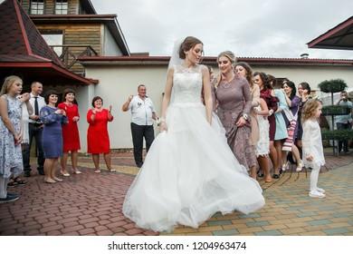 Cuman, Volyn / Ukraine - April 29 2018: Happy bride and bridesmaids dancing and having fun next to restaurant