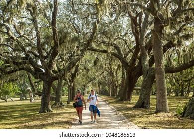 Cumberland Island, Georgia - 2/19/2018: A couple walking on a trail through a Live oak tree and spanish moss tunnel.