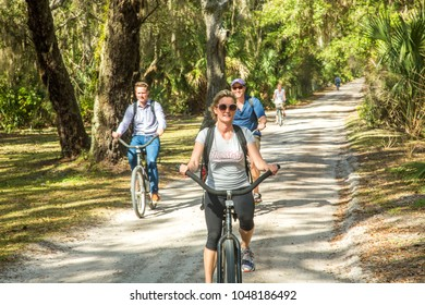 Cumberland Island, Georgia - 2/19/2018: A group of bicyclists  on a trail through a Live oak tree and spanish moss tunnel.