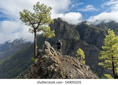 "Cumbrecita mountains in the ""Caldera de taburiente"" national park. The picture shows a photographing female backpacker at a steep rocky viewpoint of the park."