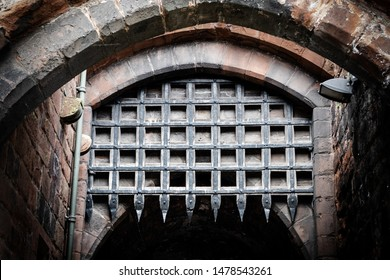 Cumbria, UK - Circa August 2019: Medieval portcullis gate seen in the opened position at the entrance to a historic building. The leaded gate frame and spikes are clearly visible in the image.