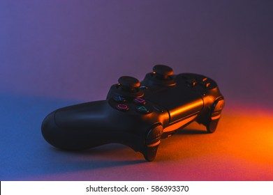 Cumbria, UK - December 21, 2016: Black Playstation 4 game controller lit with dynamic coloured lighting.