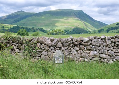 Cumbrian hills with an old-style milestone and drystone wall in the foreground, Cumbria, UK