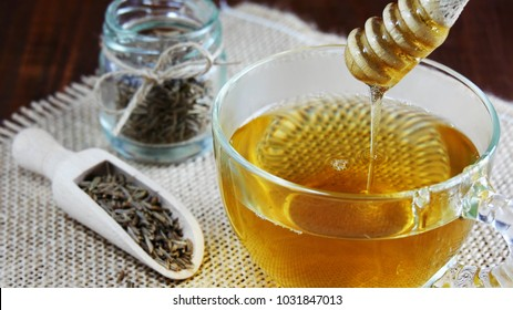 Cumin seed tea with honey, jeera water for weight loss in glass mug closeup