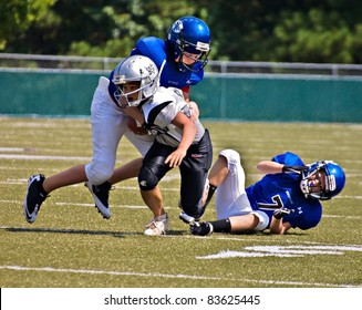 CUMMING, GA, USA - AUGUST 27 : 11 to 13-year-old unidentified boys running and tackling during a football game, the Raiders vs the War Eagles, on August 27, 2011 in Cumming GA.