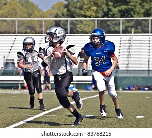 CUMMING, GA,USA - AUGUST 27:  A group of 11 to 13-year-old unidentified boys during a football game, one is ready to throw a pass, the Raiders vs the War Eagles, on August 27, 2011 in Cumming GA.