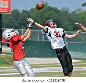 CUMMING, GA/USA - SEPTEMBER 8: Unidentified boys fighting for the pass at the goal line. Two teams of 7th grade boys September 8, 2012 in Cumming GA. The Wildcats  vs The Mustangs.