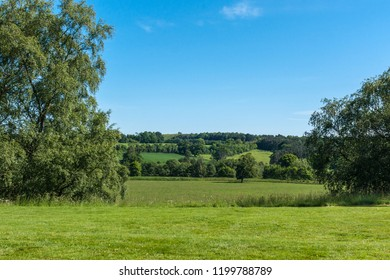 Cumnock, Ayrshire, Scotland, UK - June 18, 2012: Bucolic rural landscape with green pastures and darker forests under ble sky.