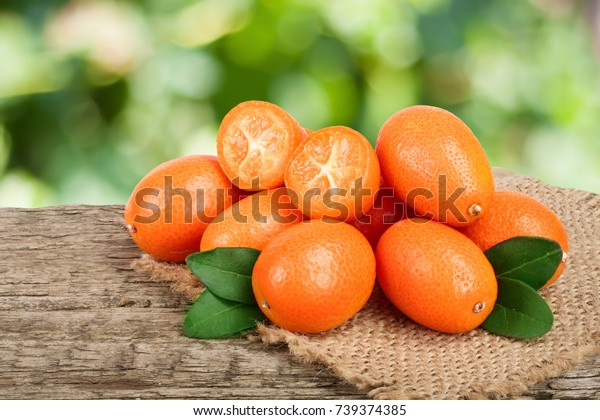 Cumquat or kumquat with leaf on old wooden table with blurry garden background