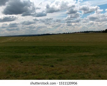 Cumulonimbus clouds in a blue sky above a grassy hill sloping from right to left