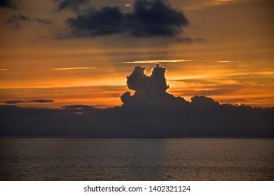 cumulonimbus clouds ocean sunset, dramatic sky atmosphere, italy mediterranean sea