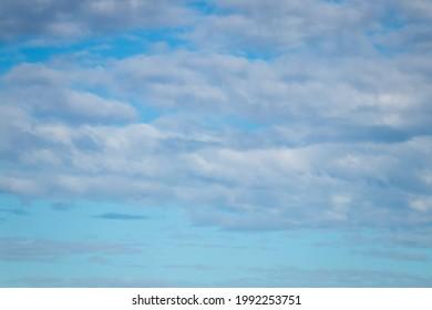 Cumulous and alto-cumulous cloud formations against a blue sky, New Zealand