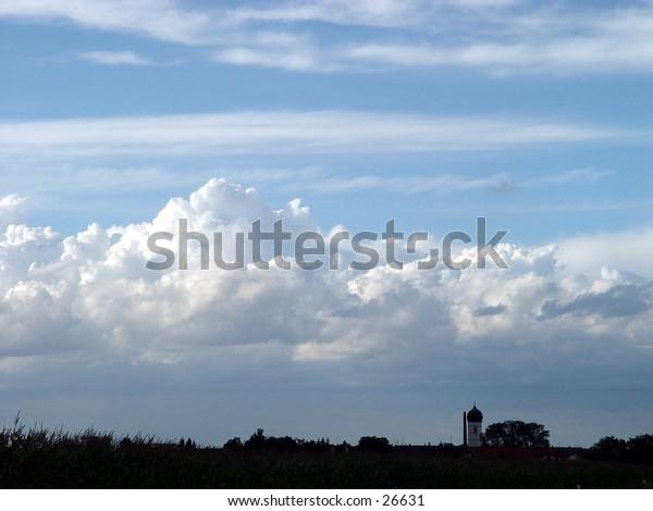 Cumulus clouds over a European church