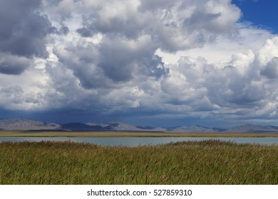 Cumulus clouds over the steppe and the lake. Lake Ulugkol. Khakassia. Russia.