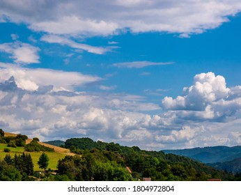 Cumulus congestus or towering cumulus - forming in the blue sky over hilly landscape