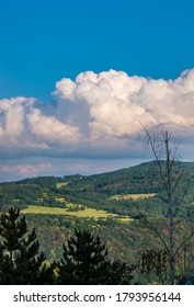 Cumulus congestus or towering cumulus - on the blue sky over hilly landscape