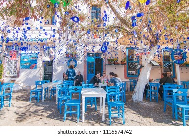 CUNDA ISLAND, AYVALIK, TURKEY - October 16, 2018: Evil eyes are hung in decorative purpose with a tree on the background in Cunda Alibey Island, Ayvalik.