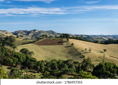 CUNHA, SAO PAULO / BRAZIL - AUG 16, 2019: Pasture and agriculture fields of neighbor ranch as saw from a higher hill inside O Contemplario farm lands under late afternoon clouded blue sky.