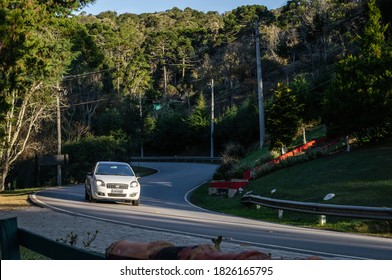 CUNHA, SAO PAULO / BRAZIL - AUG 17, 2019: A white Fiat Linea passing by a S shaped section of Salvador Pacetti road, right in front of Moara Cafe in late afternoon.