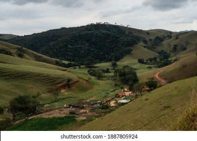 CUNHA, SAO PAULO, BRAZIL - AUG 19, 2019: A farm lost in between the mountainous Sea Ridge (Serra do Mar) as saw in the way to Pimenta waterfall in the countryside of Cunha and under overcast sky.