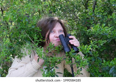 cunning curious European adult woman close-up, holding black field binoculars with zoom, hiding in greenery, peeping from green bushes, spying on unfaithful husband, neighbors