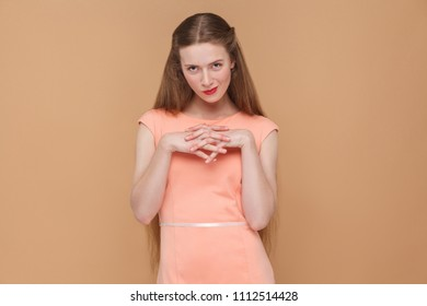 cunning plan, looking at camera. portrait of emotional cute, beautiful woman with makeup and long hair in pink dress. indoor, studio shot, isolated on light brown or beige background.
