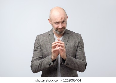 Cunning tricky mature man thinking with hand together over white background. Concept of unfair game