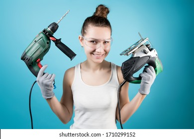 A cunningly smiling girl and power tools in her hands - a jigsaw and a drill. Isolated on blue