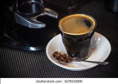 A Cup of Caffè Americano and The Coffee Beans On a Dark Pattern Background