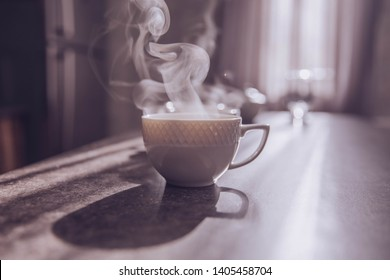 Cup of americano on a table. Steam from hot coffee rises up