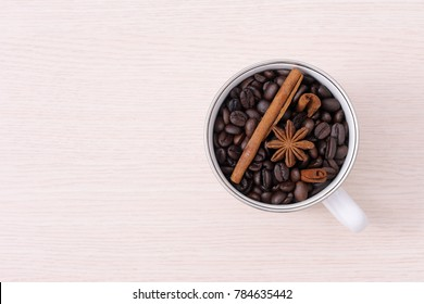 Cup of aroma coffee beans, cinnamon and anise spicy on wooden table.