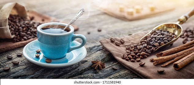 A cup of aromatic black coffee and coffee beans on the table. Morning Coffee Espresso for breakfast in a beautiful blue cup.