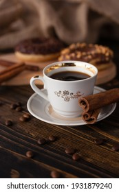 A cup of aromatic black coffee, grains of different varieties on the table. Morning espresso or Americano coffee for breakfast in a beautiful cup. Still life. Cinnamon sticks. Delicious donut on a woo